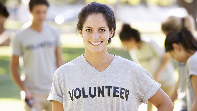 Young woman smiling, wearing a gray volunteer shirt.