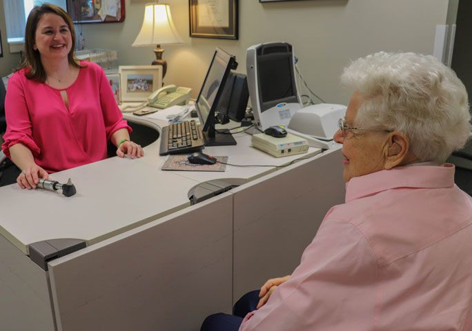 Senior woman talking with a doctor sitting at a desk.