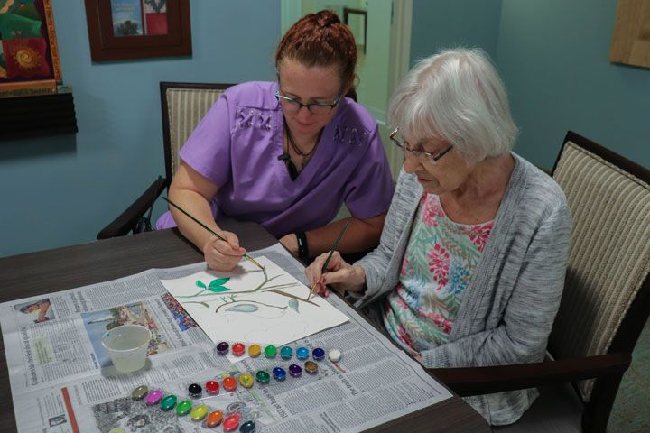Nurse and senior painting together.