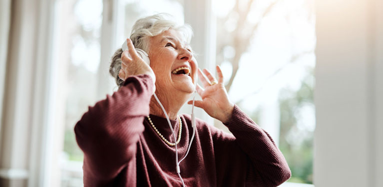 Senior woman smiling while wearing headphones.