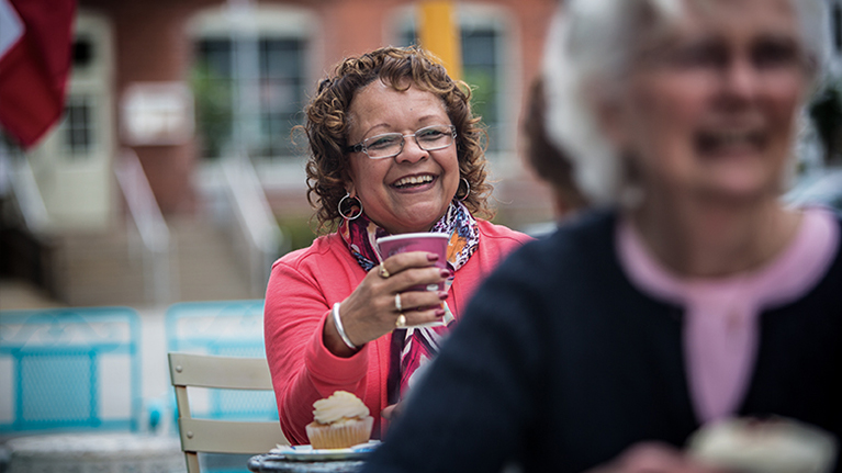 Woman smiling and laughing in a pink sweater while holding a coffee cup