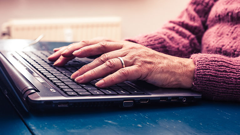 Senior women wearing wedding ring, typing on a laptop.