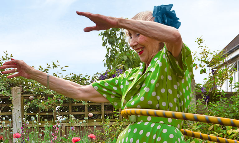Senior woman laughing outside community gardens