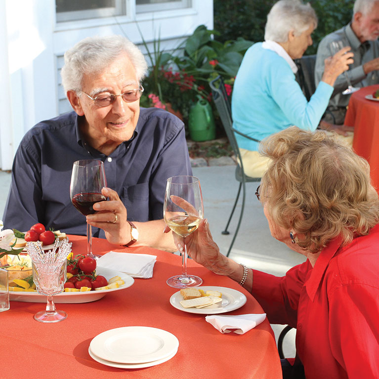 Two Masonicare residents enjoy a glass of wine with dinner outside.