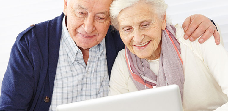 Senior man and woman looking at computer screen.