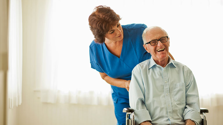 Nurse pushing a smiling senior man in a wheelchair.