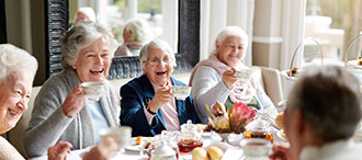 Three older women smiling holding up their tea cups