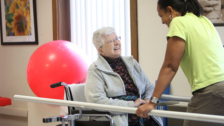 An elderly lady in a wheel chair looking up at a short term rehab instructor.