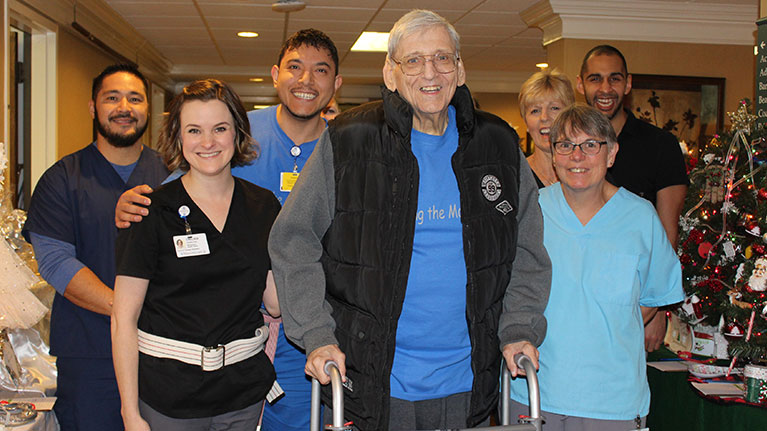 Older man smiling while holding onto his walker. Six employees at Masonicare also smiling behind him.
