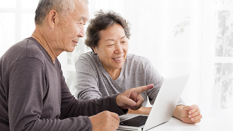 Senior couple smiling and pointing at laptop screen.