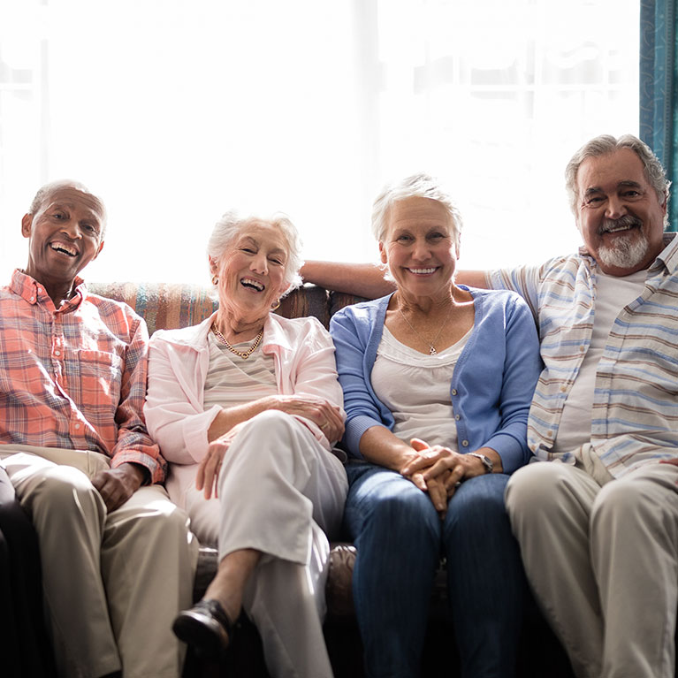 Two older couples smiling, relaxing on the couch together
