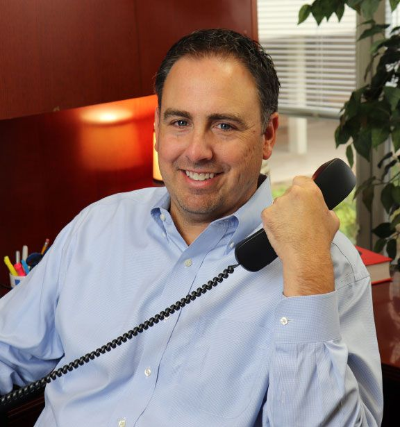 A photo of Edward Dooling, Vice President Human Resources. Smiling holding a desk phone