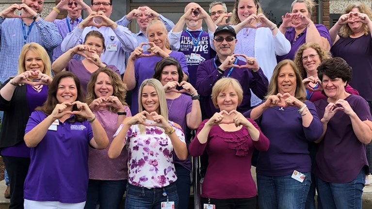 Group of men and women wearing purple, making heart shapes with their hands.
