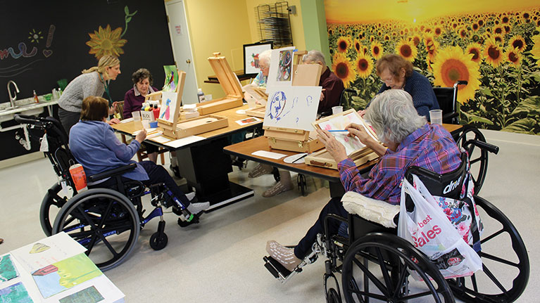 Older ladies in wheel chairs partaking in Arts and Crafts at Masonicare