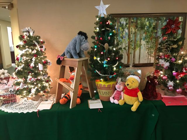 Three decorated Christmas trees with Whinney The Pooh stuffed characters.