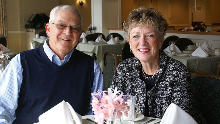 Senior couple smiling while sitting at a dining room table.