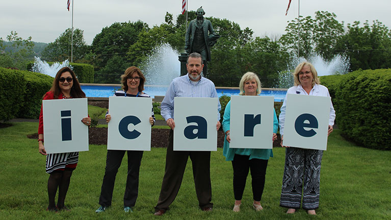 Four women and one man outside holding signs that spell icare.