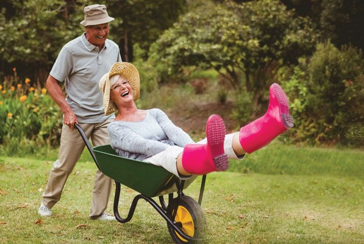 Senior man pushing senior woman laughing in wheelbarrow.