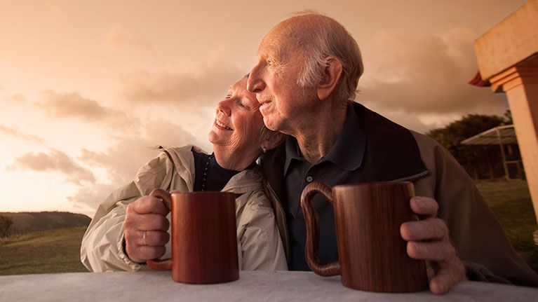 Picture of older couple sitting down holding their coffeemugs while looking out into the field and sunset.