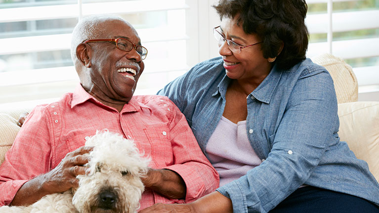Senior couple laughing while sitting with a dog.