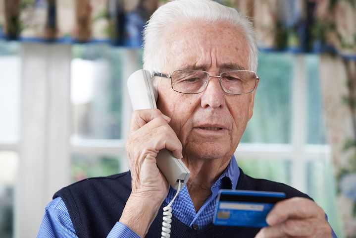 Senior man talking on the phone while holding a credit card.