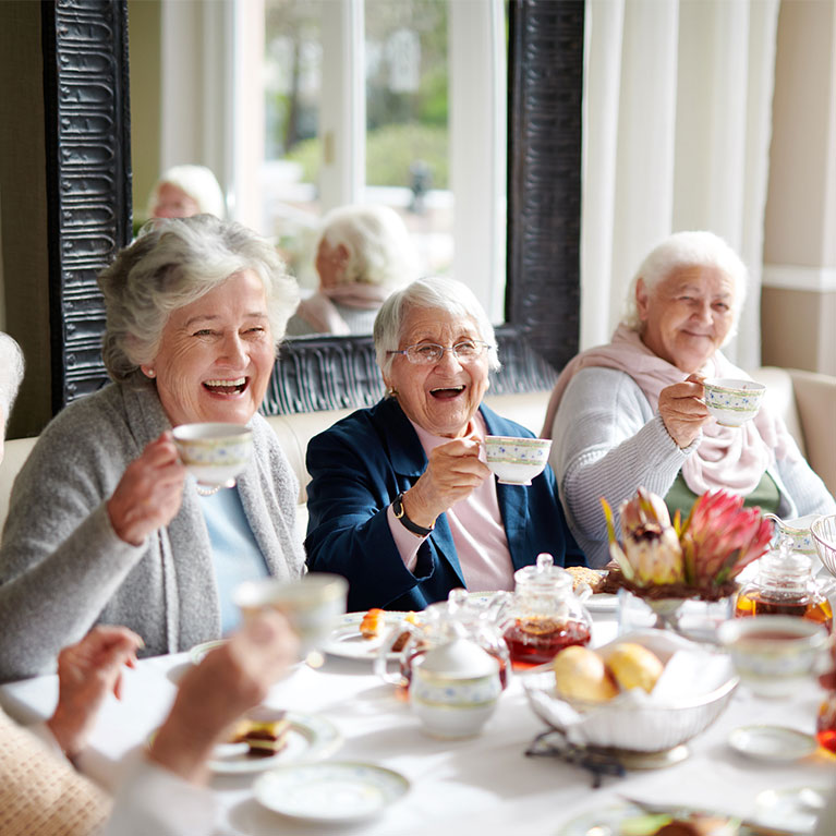 Three older women laughing holding their tea cups up in the air