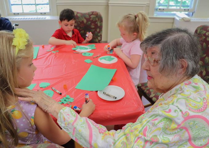 Senior woman helping three children make crafts.