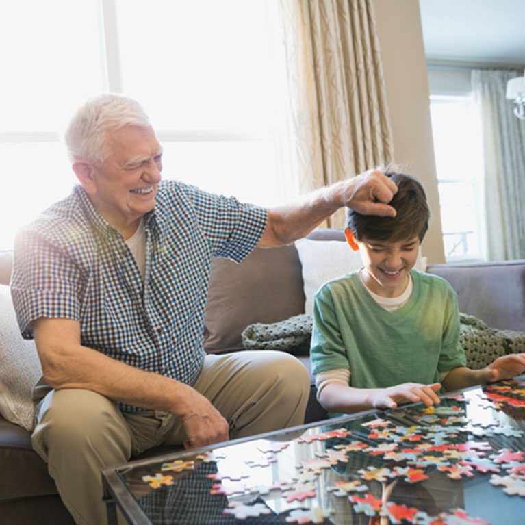 Grandfather and Grandson laughing while playing with a puzzle