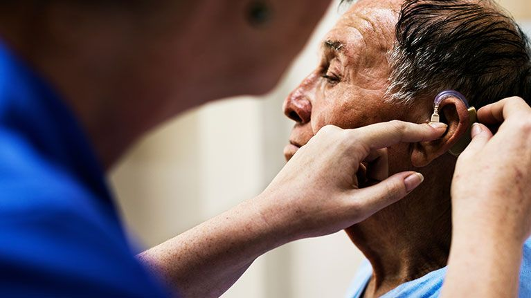 A male doctor or nurse putting a hearing aid into an older man  who is his patients ear.