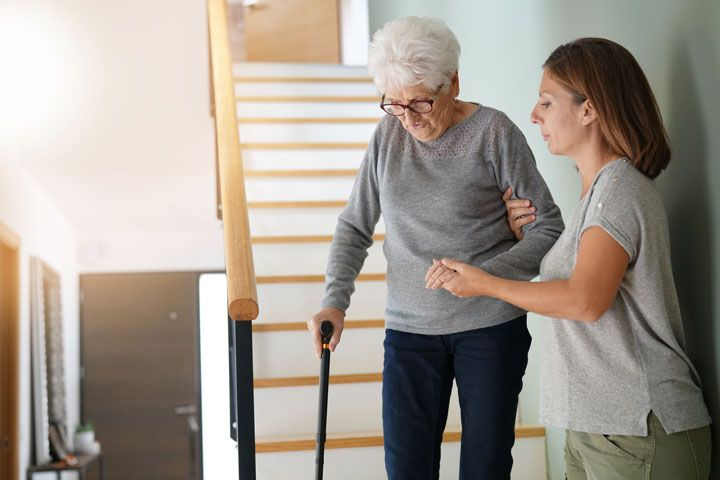 Woman helping senior walk down the stairs.