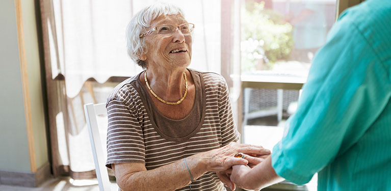 Older woman smiling looking at her nurse