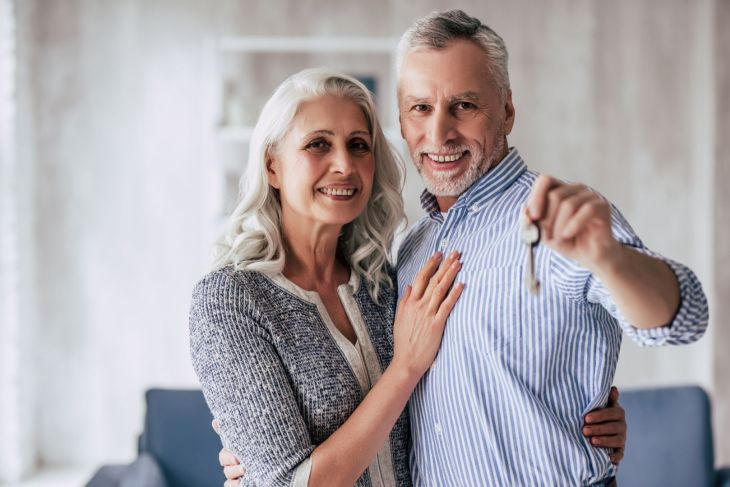 Older couple hugging and smiling holding a key