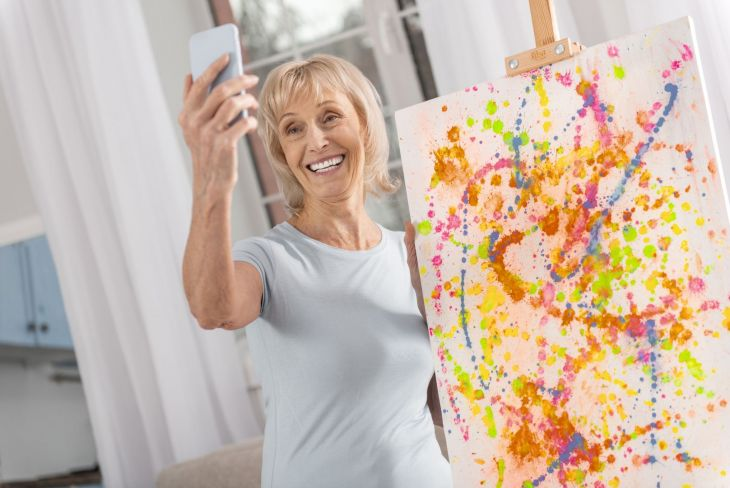 A woman taking a selfie in front of her artwork