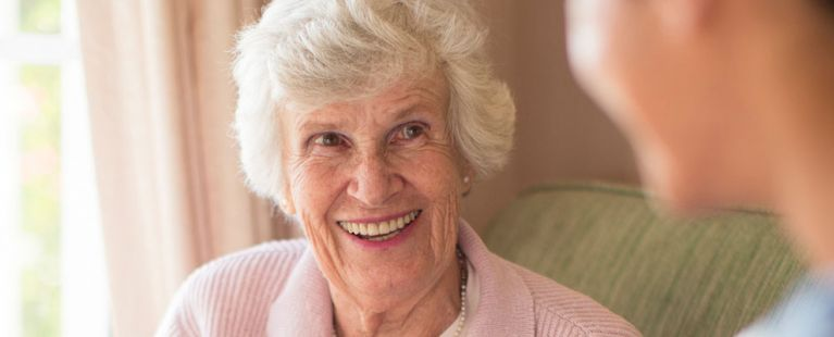 Senior woman smiling with assisted living nurse