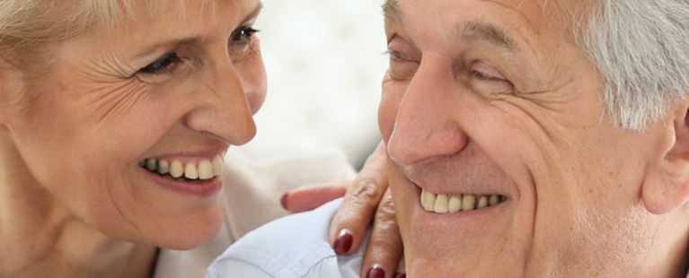 Senior couple smiling at each other.