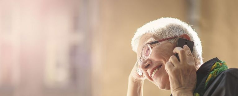 Senior smiling while talking on cell phone