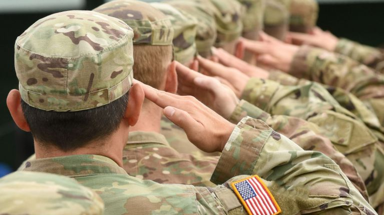 Active service members saluting