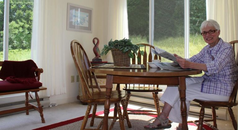 Resident enjoying the sunroom in her cottage